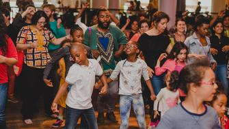 Photo of children and adults joining in a dance workshop together at Southbank Centre