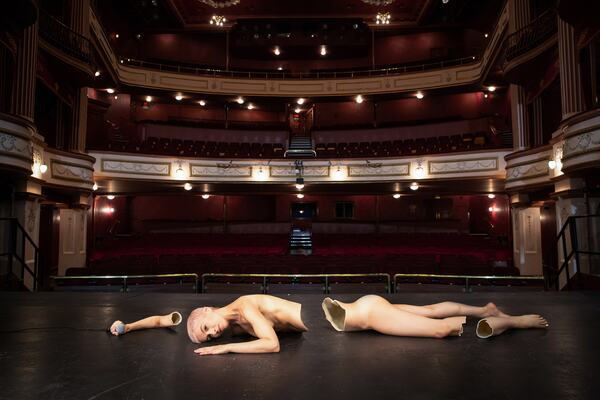 In a photo by fine art photographer Suzie Larke, a nude woman lies face-down on the stage of an empty auditorium. The woman, who looks anxious, is holding a microphone in her outstretched right hand. Her body is broken into four pieces and appears to be made from porcelain. Image credit: Storms Don't Last Forever © Suzie Larke.