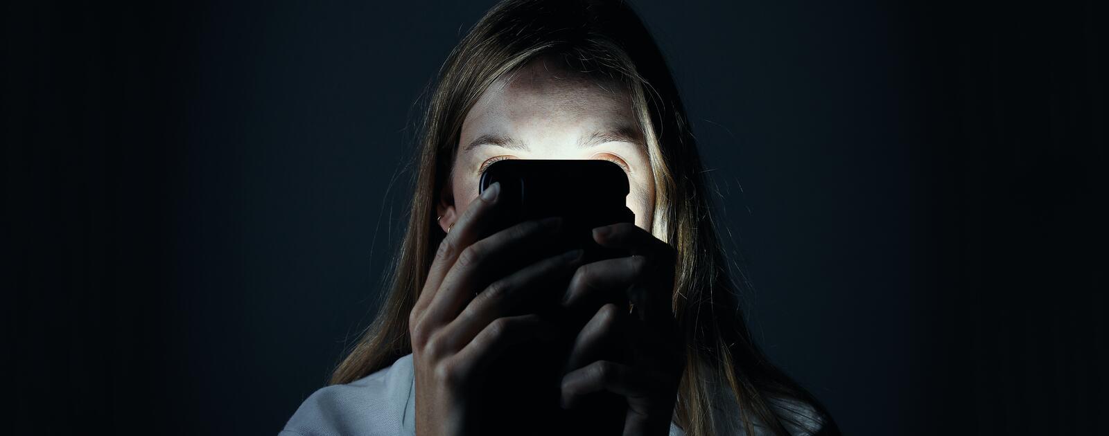 A girl behind a phone screen