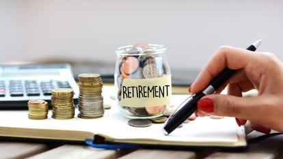 Concept of retirement planning with woman putting coins in glass jar for pension