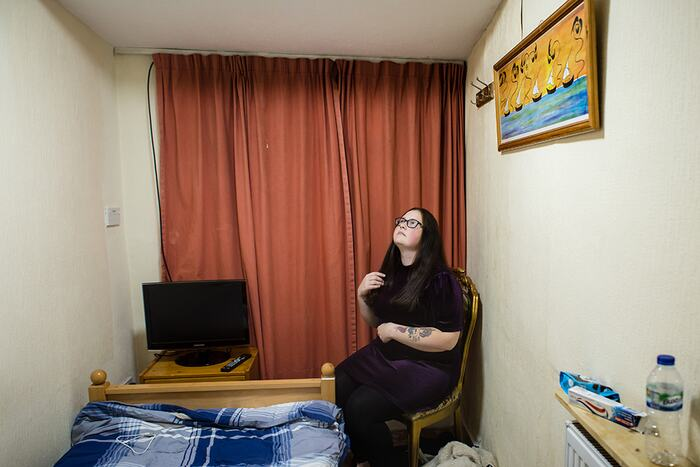 Photograph submitted by Cocoa Laney for the 'Inspired by Arbus' photography competition run by Southbank Centre with UAL. The photo depicts a young woman in a bedroom in a budget hotel by London's Victoria Station
