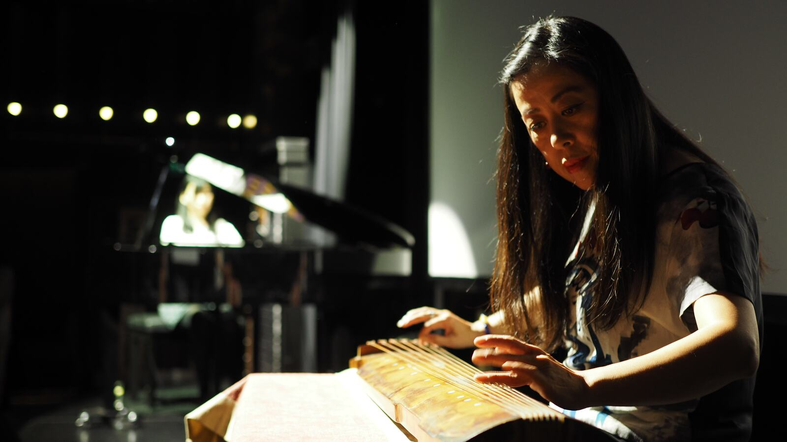 Performer playing the guqin on-stage