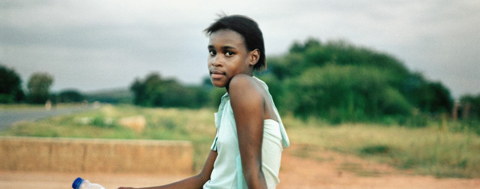 Homeland, Nklele Machika or Mary Koketse, Sehoko, former Bophuthatswana (2010) a photograph by Thabiso Sekgala depicting a young woman sitting on a concrete wall