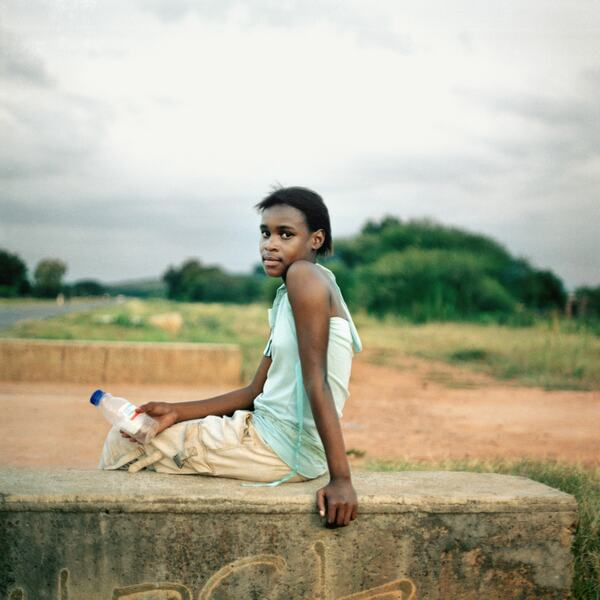 Homeland, Nklele Machika or Mary Koketse, Sehoko, former Bophuthatswana (2010) a photograph by Thabiso Sekgala depicting a young woman sitting on a concrete wall