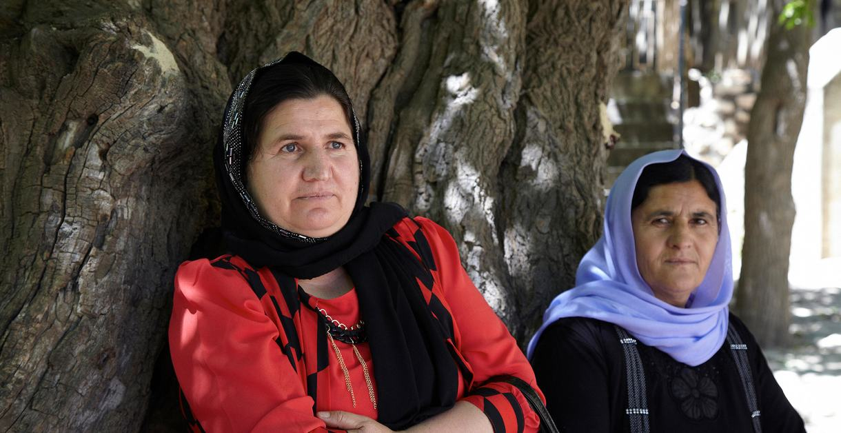 FKE3TY Two yazidi women resting beside a old tree in Lalish, Yazidis Holy temples in Kurdistan Iraq.