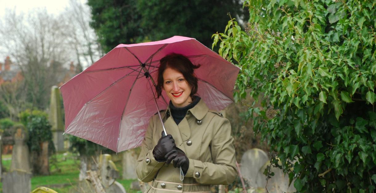 Julie Cohen holding an umbrella in a cemetery
