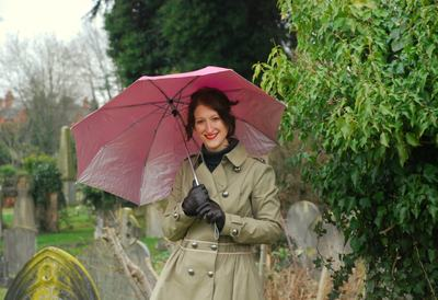 Julie Cohen holding an umbrella in a cemetery