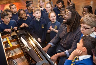 School children singing next to a piano