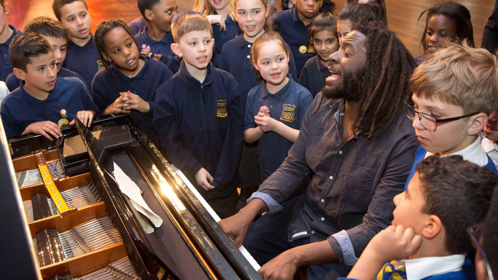 School children singing next to a piano