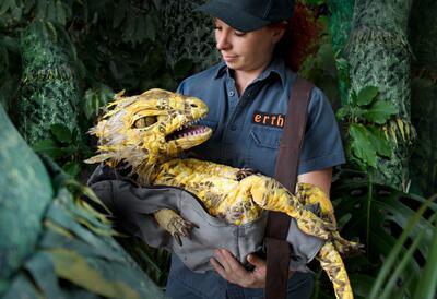 Zookeeper hodling a dinosaur