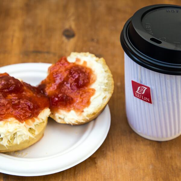 Photo of a scone covered in clotted cream on the bottom and jam on top, next to a takeaway cup of tea, served by Tea, Bread & Brownie at Southbank Centre Food Market