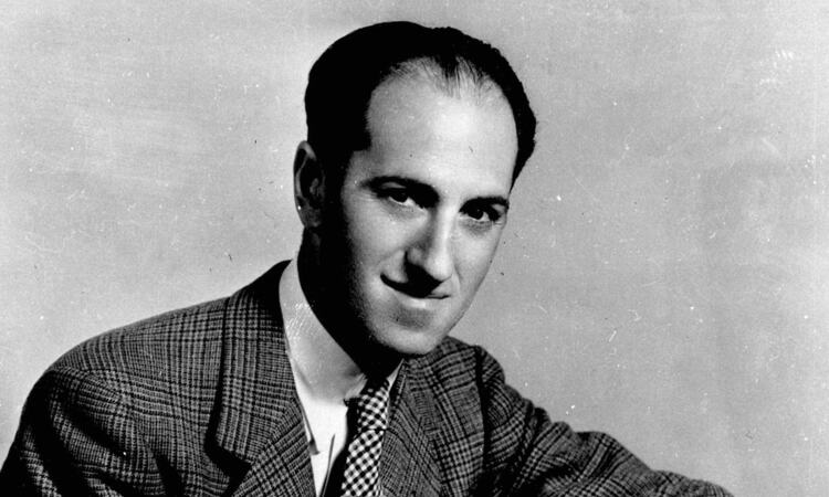 George Gershwin composer, seated at his piano