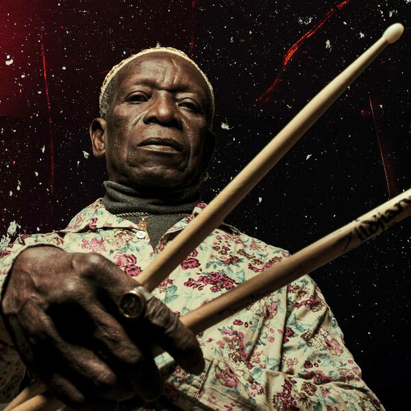 The late Tony Allen holding drumsticks