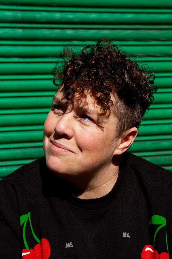 This is a picture of Jess Thom – a white woman with curly brown hair in front of some metallic green shop shutters on a sunny afternoon. Jess is looking up and smiling just off camera. She is wearing a black sweatshirt with a colourful red cherry repeat print.
