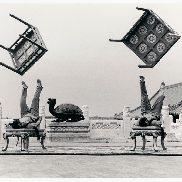 Black and White Photograph of two gymnasts throwing tables in the air with their feet