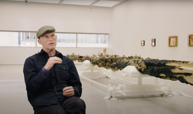 Matthew Barney sits talking to camera in his exhibition Redoubt at Hayward Gallery