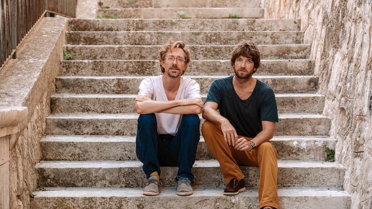 Kings of Convenience, folk duo Erlend Øye and Eirik Glambek Bøe sitting on steps