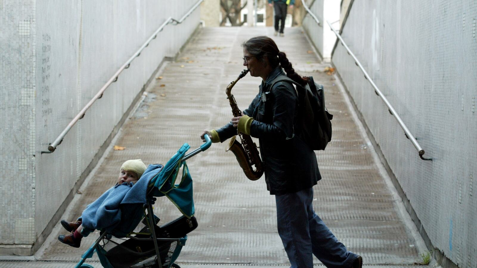 A man with saxophone pushing a child in a buggy