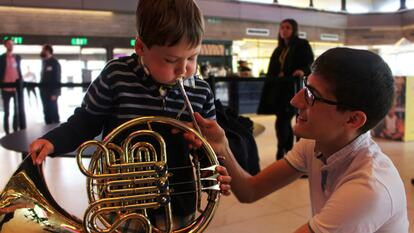 A Young Boy Taught to Play French Horn at a workshop