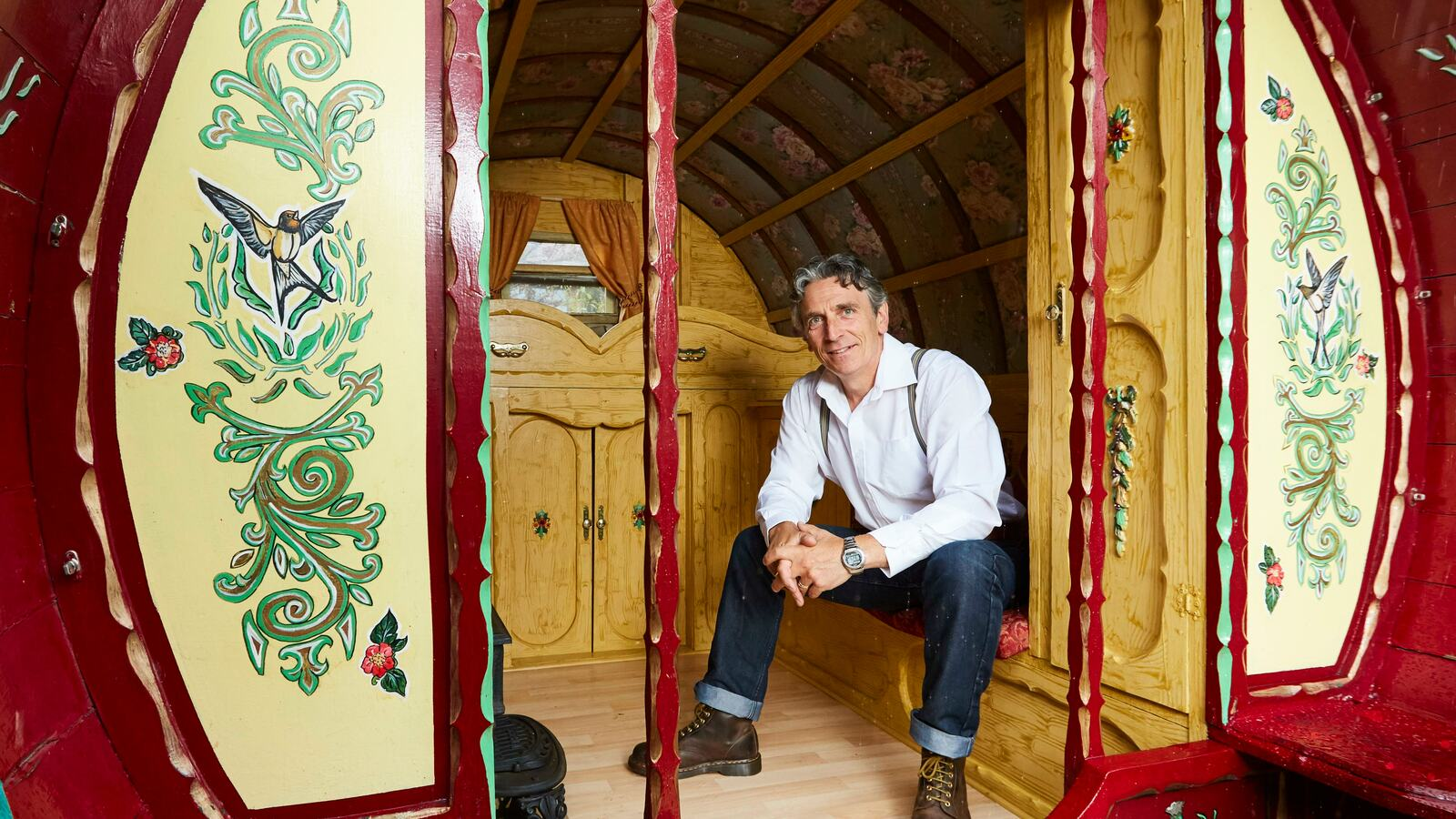 Photo of storyteller Richard O'Neill sitting inside a traditional Romany caravan