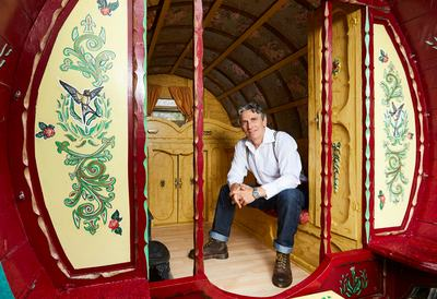 Photo of storyteller Richard O'Neill sitting inside a traditional Romany caravan