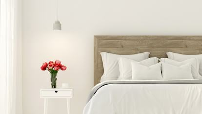 3D illustration. Interior of the bedroom in white colour and with tulips on the bedside table
