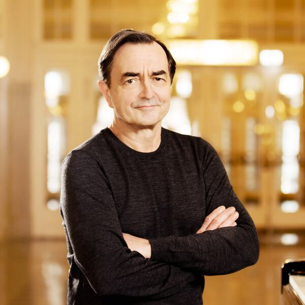 Pianist Pierre-Laurent Aimard standing next to a piano