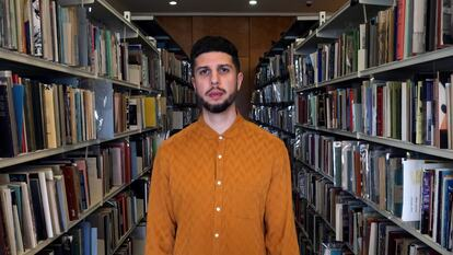 Poet Anthony Anaxagorou stands in the National Poetry Library at Southbank Centre