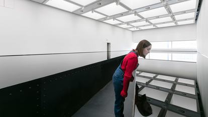 Visitor looking over Richard Wilson: 20:50, (1987) at Space Shifters at the Hayward Gallery