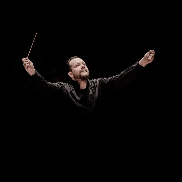 Conductor Andris Nelsons with open arm waving the baton