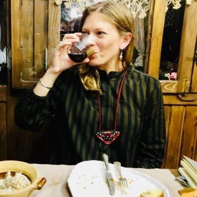 Caroline Eden drinks from a glass whilst seated at a restaurant table