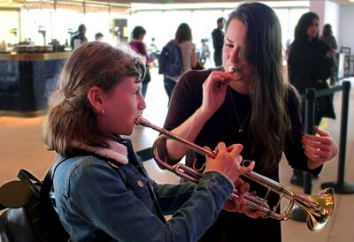A Young Girl Taught to play a Trumpet at a Workshop
