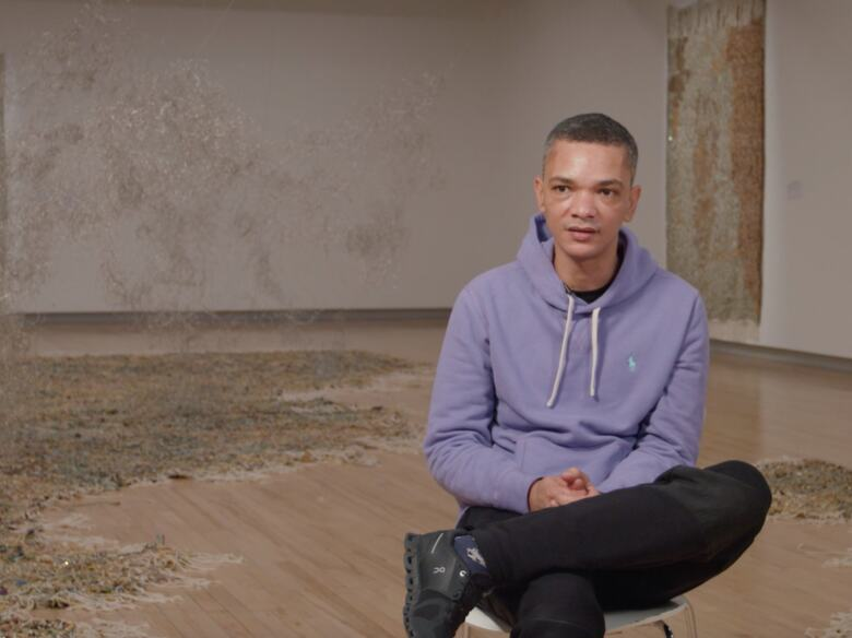 The artist Igshaan Adams sits cross-legged on a chair in the middle of his Hayward Gallery installation Kicking Dust as he talks to camera during an interview