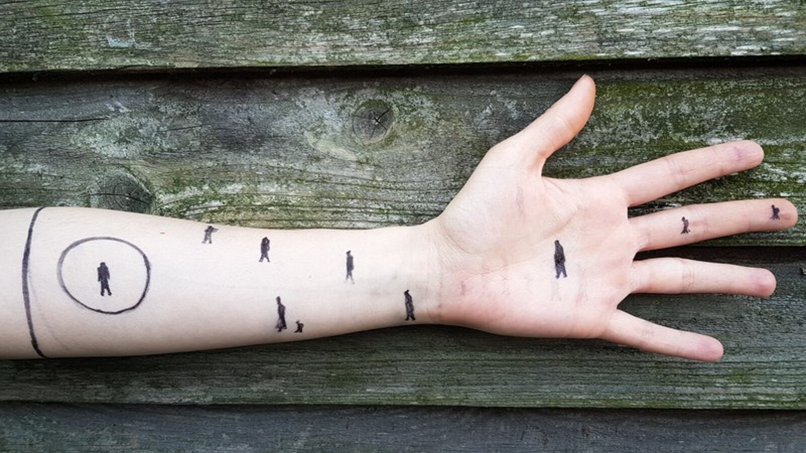 An arm and hand with small illustrations drawn on