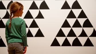 A young girl looks at one of Bridget Riley's artworks in Hayward gallery
