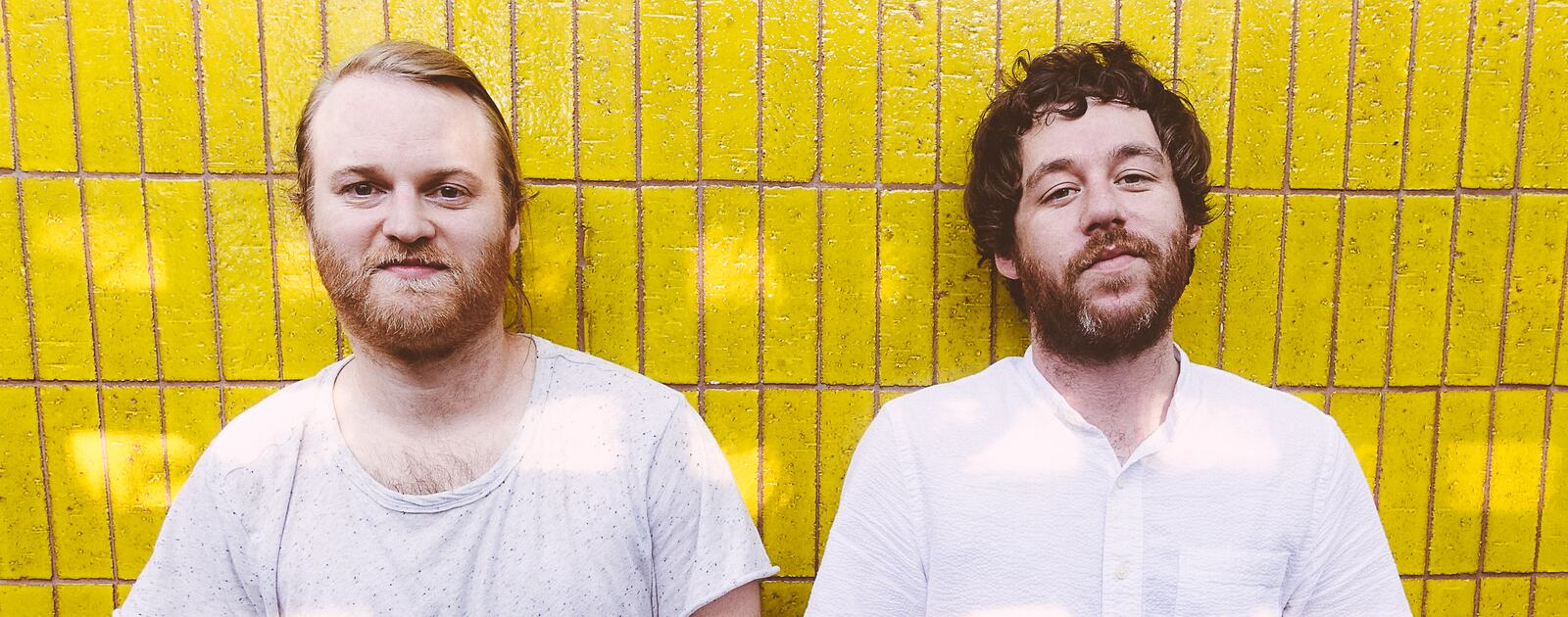 Michael Stein and Kyle Dixon stand in front of a yellow wall