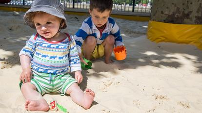 Photo of two small children sitting in the sand on Southbank Centre's beach