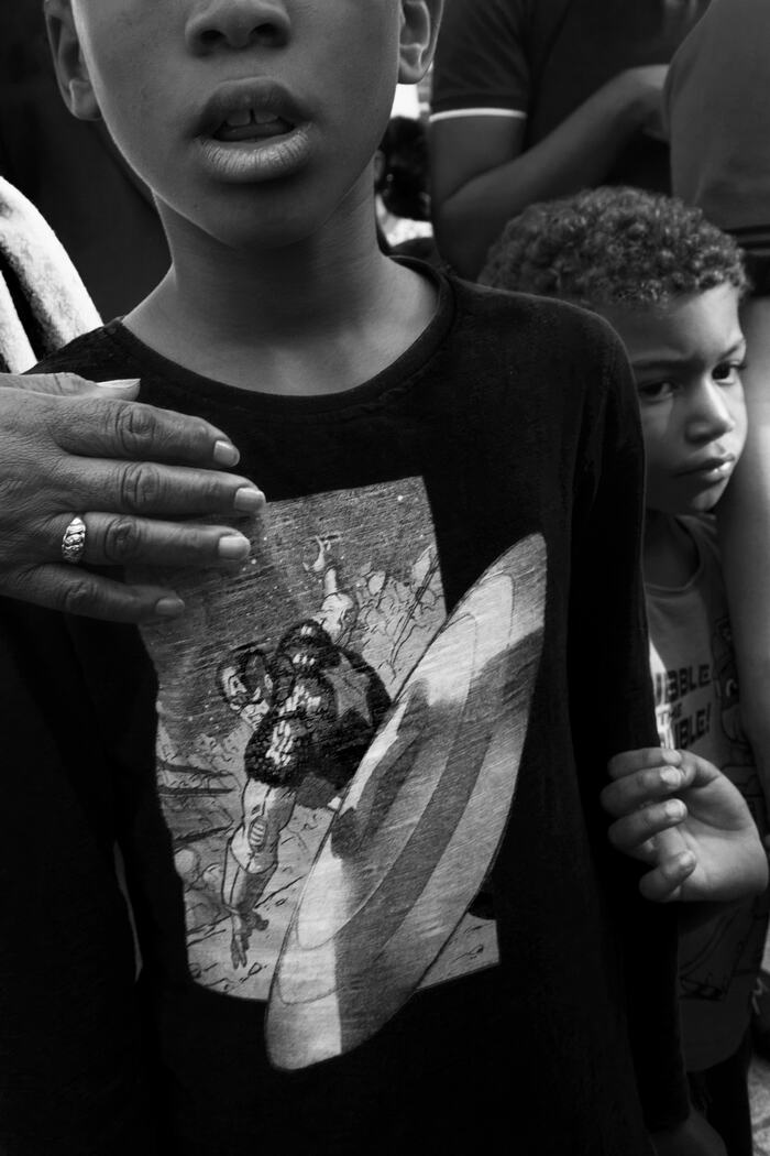 Photograph submitted by Theresa Maria Forthaus for the 'Inspired by Arbus' photography competition run by Southbank Centre with UAL. Photograph depicts two young boys standing in a crowd, in Southwark, South London.
