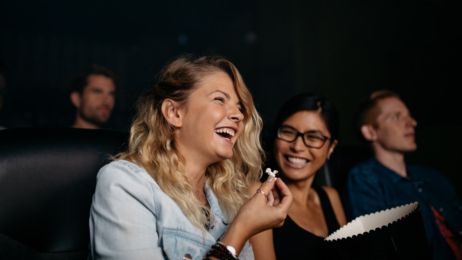 Group of people watching movie in theater. Girls laughing and watching comedy movie.