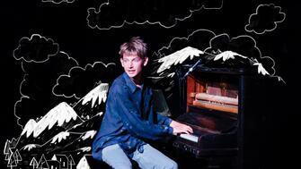 A boy playing a piano
