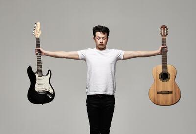 Sean Shibe holding his guitars