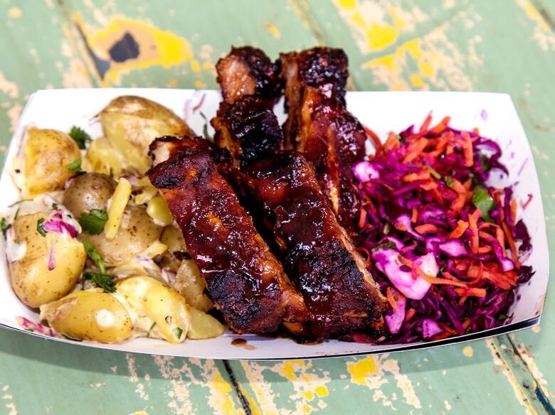 Photo of a dish of glazed ribs, potato salad and slaw served by Street Pig BBQ at Southbank Centre Food Market