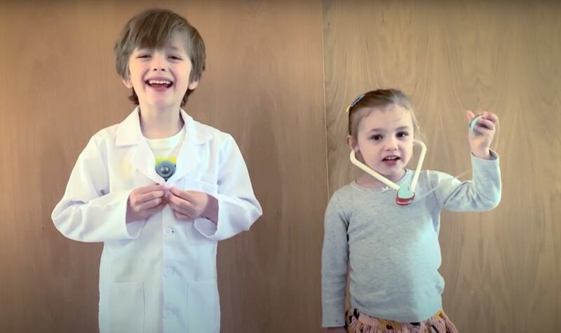 Two young children dressed as doctors read a line from the poem 'Dear Key Workers'