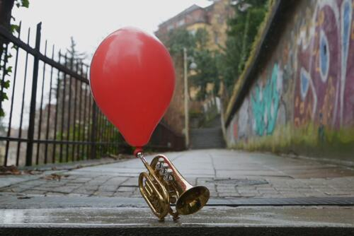 Balloon attached to a trumpet outside