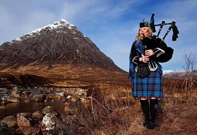 Female Highland Piper in full Highland dress piping in Glencoe, Scotland