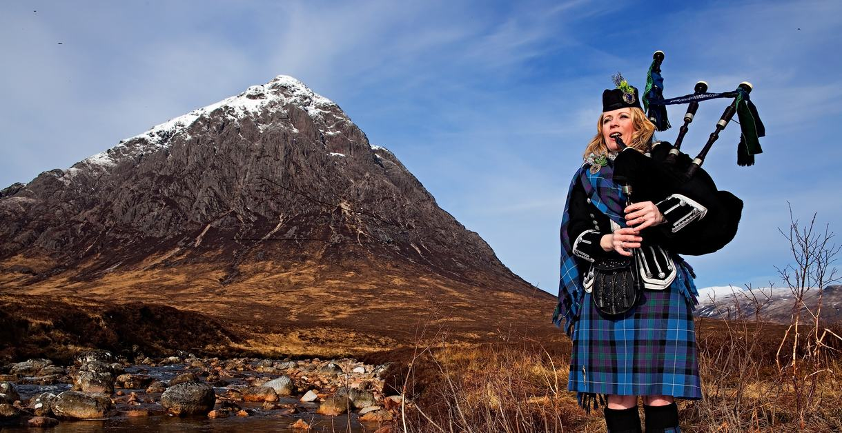 Female Highland Piper in full Highland dress piping in Glencoe, Scotland