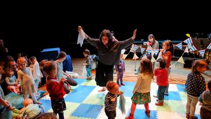Photo of a performer surrounded by small children as part of the show Far, Far Away