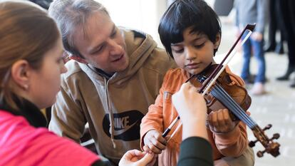 Child playing the violin in a workshop