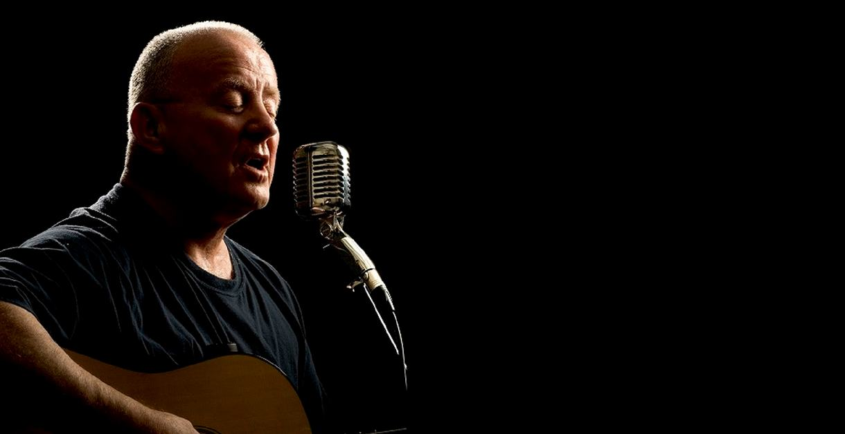 Christy Moore with his guitar singing into a microphone