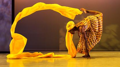 Photograph of a dancer performing with a long yellow headscarf swirling around her, to promote the Head Wrap Bar at Southbank Centre's Africa Utopia festival